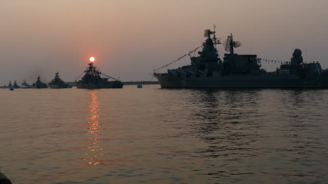 beautiful sunset in a bay with silhouettes of warships