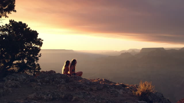 Beautiful sunset overlooking the Grand Canyon as sister helps her twin stand
