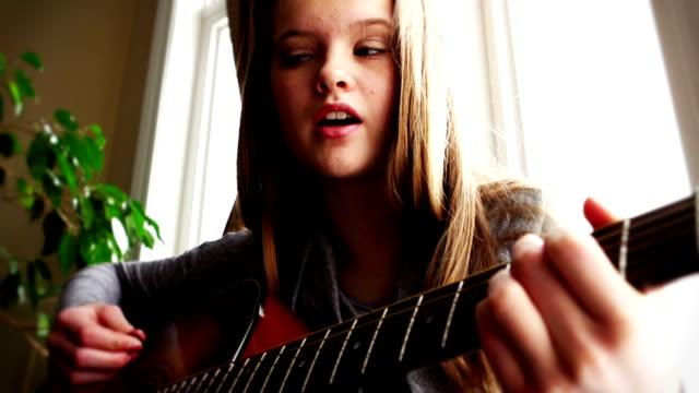 Beautiful teenager playing guitar