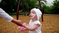 Beautiful toddler girl reaches for mom to pick her up at park