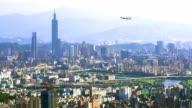 Beautiful view of an airplane flying over Taipei city at sunset