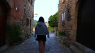 Beautiful view of traveler woman walking in the unique town of Siurana in the Tarragona mountains during summer vacations in the Catalonia region.