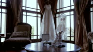 Beautiful white bridal shoes and dress at luxurious bedroom
