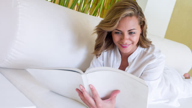 Beautiful woman at a hotel reading a book