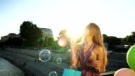 Beautiful woman blowing soap bubbles