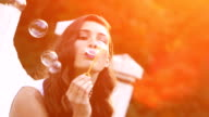 Beautiful woman blows bubbles 5