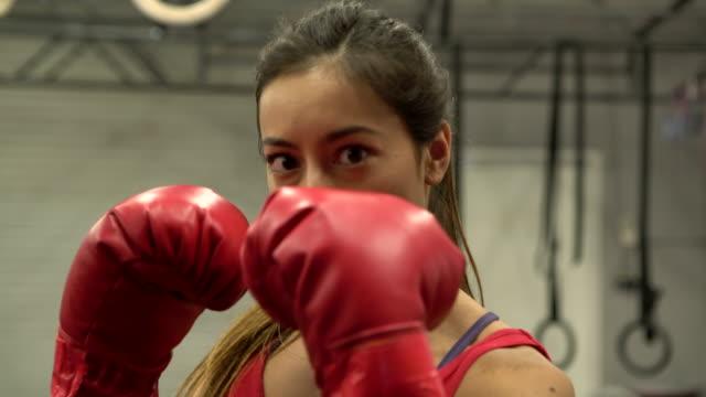 CU beautiful woman boxing in a gym