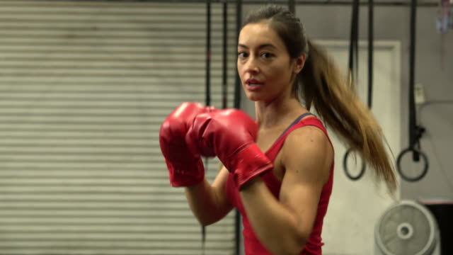 MS beautiful woman boxing with red boxing gloves in a gym