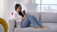 Beautiful woman chatting on her smartphone relaxing at home