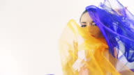 Beautiful woman dancing in colored silk. Slow motion.