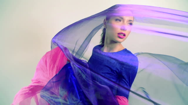 Beautiful woman dancing in colored silk. Slow motion.