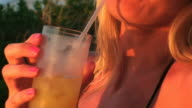 Beautiful woman drinking a cocktail in the sunset lights