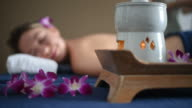 Beautiful woman enjoying aromatherapy oil massage in spa salon.