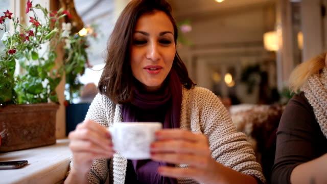 Beautiful woman enjoying coffee and talking to someone