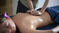 Beautiful woman getting a hot stone massage in spa salon.