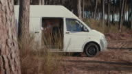 Beautiful woman getting dressed in the back of her van and walking into forest in the morning in the South of France.