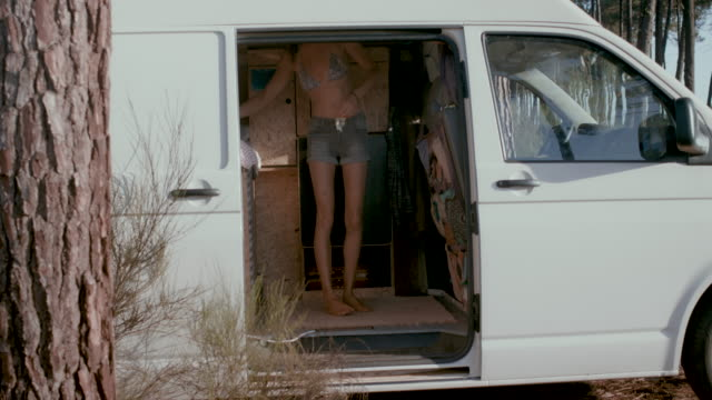 Beautiful woman getting dressed/changing clothes in the back of her van in the morning in the South of France.
