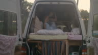 Beautiful woman getting up in the morning in motor home in the summer in the forest in the South of France.