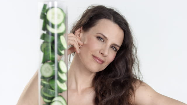 beautiful woman - glass-tube filled up with cucumber slices in foreground