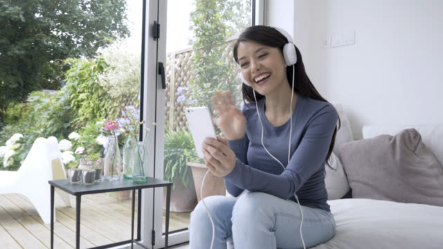 Beautiful woman having a live video chat with a friend wearing headphones