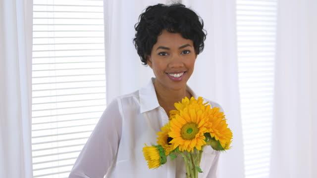 Beautiful woman holding sunflowers by window