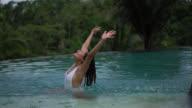 Beautiful woman in an infinity pool happy splashing water