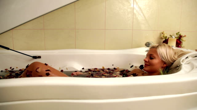 Beautiful woman in jacuzzi with flower petals