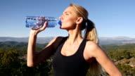 Bella donna guardando lontano e acqua potabile