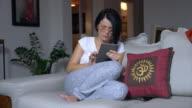 beautiful woman looking pad on sofa at home