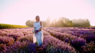 SLO MO Beautiful woman relaxing among lavender flowers