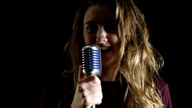 Beautiful woman singing to the microphone in a studio