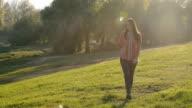 Schöne Frau zu Fuß in der Natur und hören Musik auf smartphone