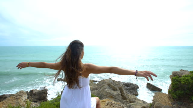 Beautiful woman with the arms raised alone in nature