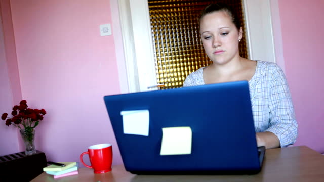 Beautiful woman working on a laptop and drinking coffee