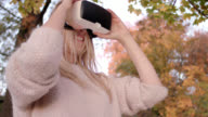 beautiful women in her mid thirties with long blond hair / using VR glasses in front of autumnal trees / shot-2