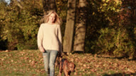 beautiful women with long blond hair in her mid thirties with her brown dog on a leather leash / close-shot