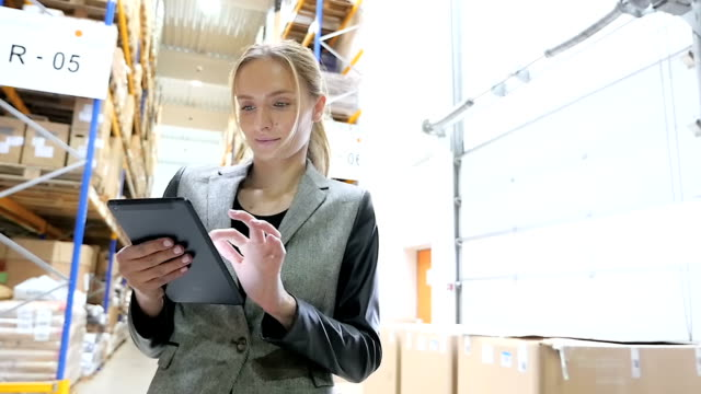 Beautiful worker using tablet in warehouse