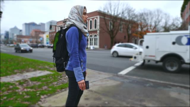Mooie jonge volwassen vrouwelijke immigranten kijken auto's pass door