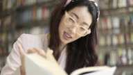 Beautiful young Asian woman happily reading a book