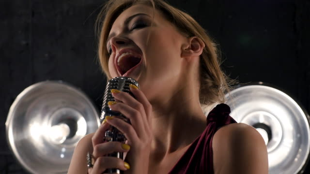 Beautiful young female vocalist singing into retro microphone