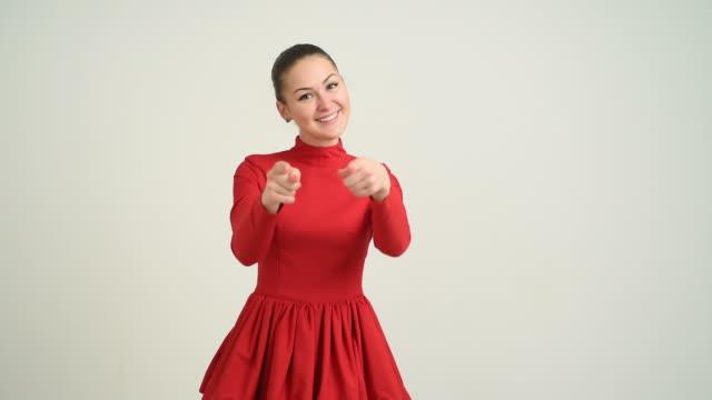 Schöne junge Mädchen in einem roten Kleid zeigt Textfreiraum und zeigt seine Daumen auf einem grauen Hintergrund