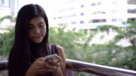Beautiful young girl uses a smartphone on a city background.