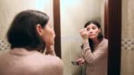 Beautiful young woman applying cosmetics.