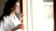 HANDHELD: Beautiful young woman in bathrobe by the window