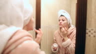 Beautiful young woman in bathroom applying moisturizer.