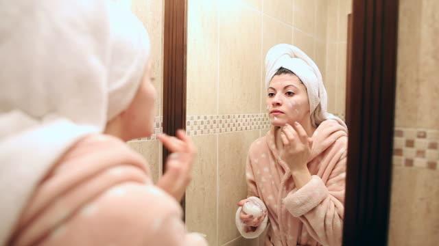 Beautiful young woman in bathroom applying moisturizer.