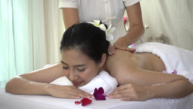 Beautiful young woman receiving back oil massage