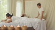 Beautiful young woman receiving legs massage