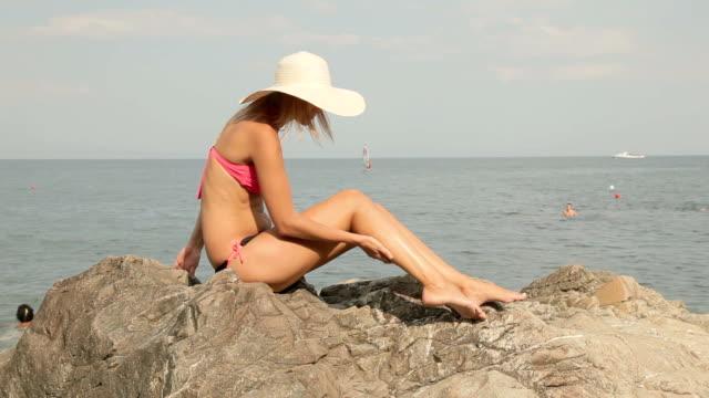 beautiful young woman sitting on rock at beach, taking sunbath
