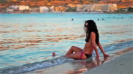 Bellissima giovane donna in piedi sul mare guardando il tramonto a Malta